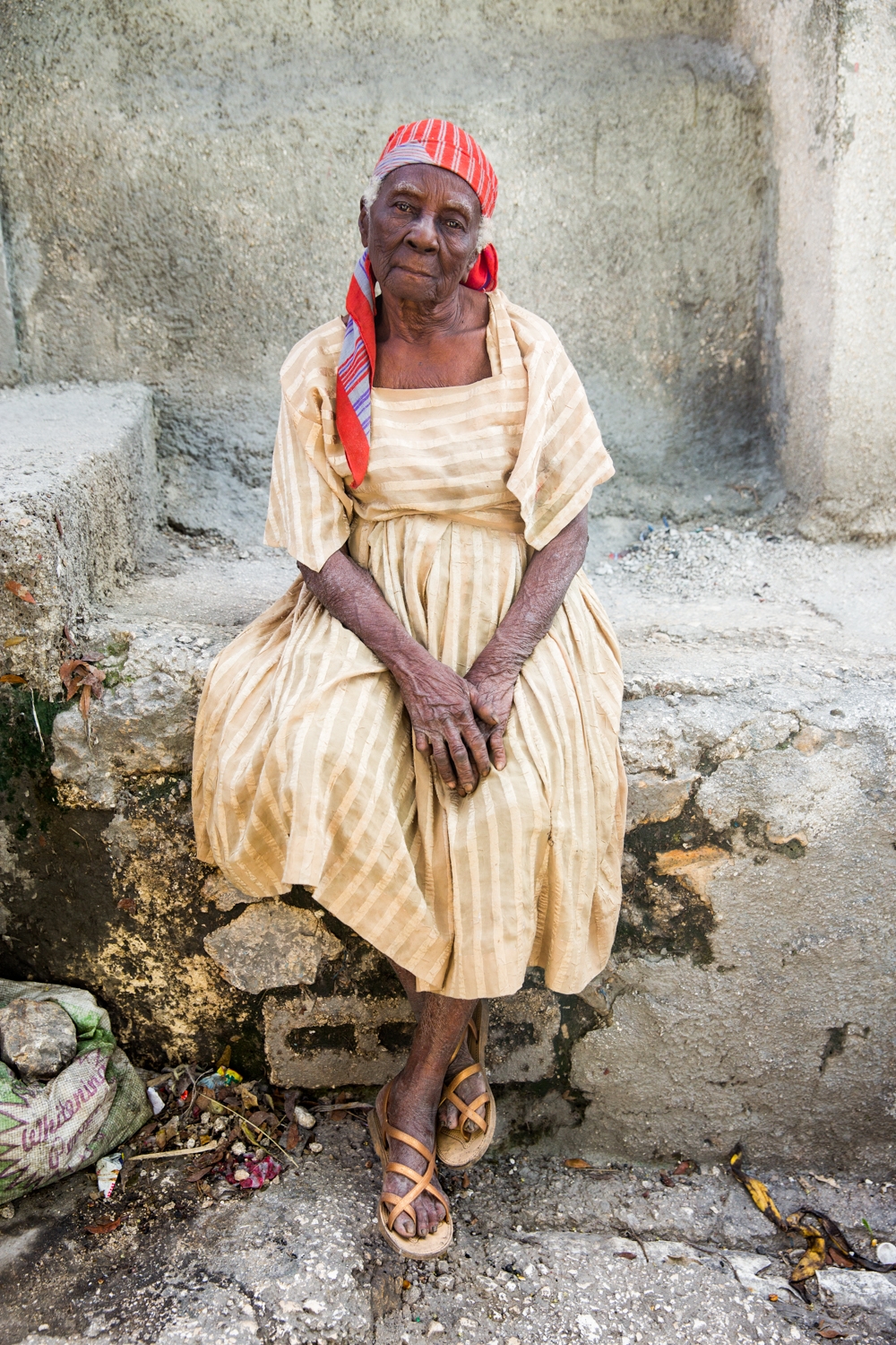 Frerisena Lagerre wearing a gold pin striped dress sits down to pose for a photo in Jalouzi, Petion-Ville.