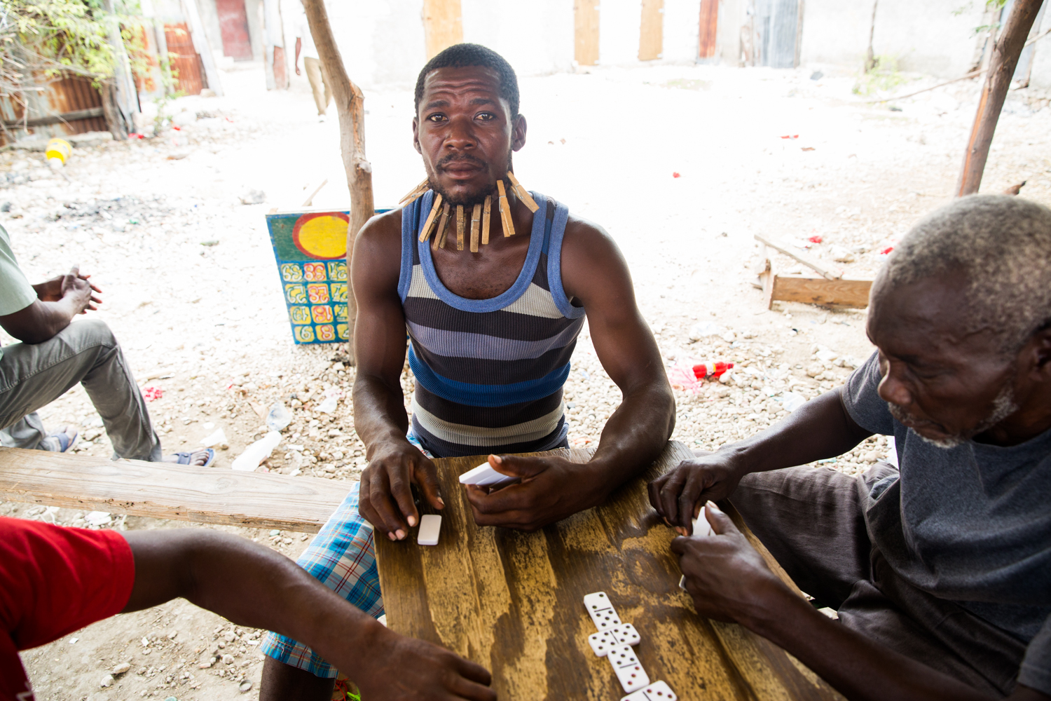 A man plays bourik in Croix-des- Bouquets. Bourik is Haitian dominos. If you lose, you put a close pin on your face.