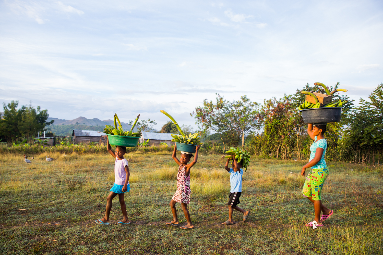 A family of banana farmers walk at sunrise in Central Plateau.