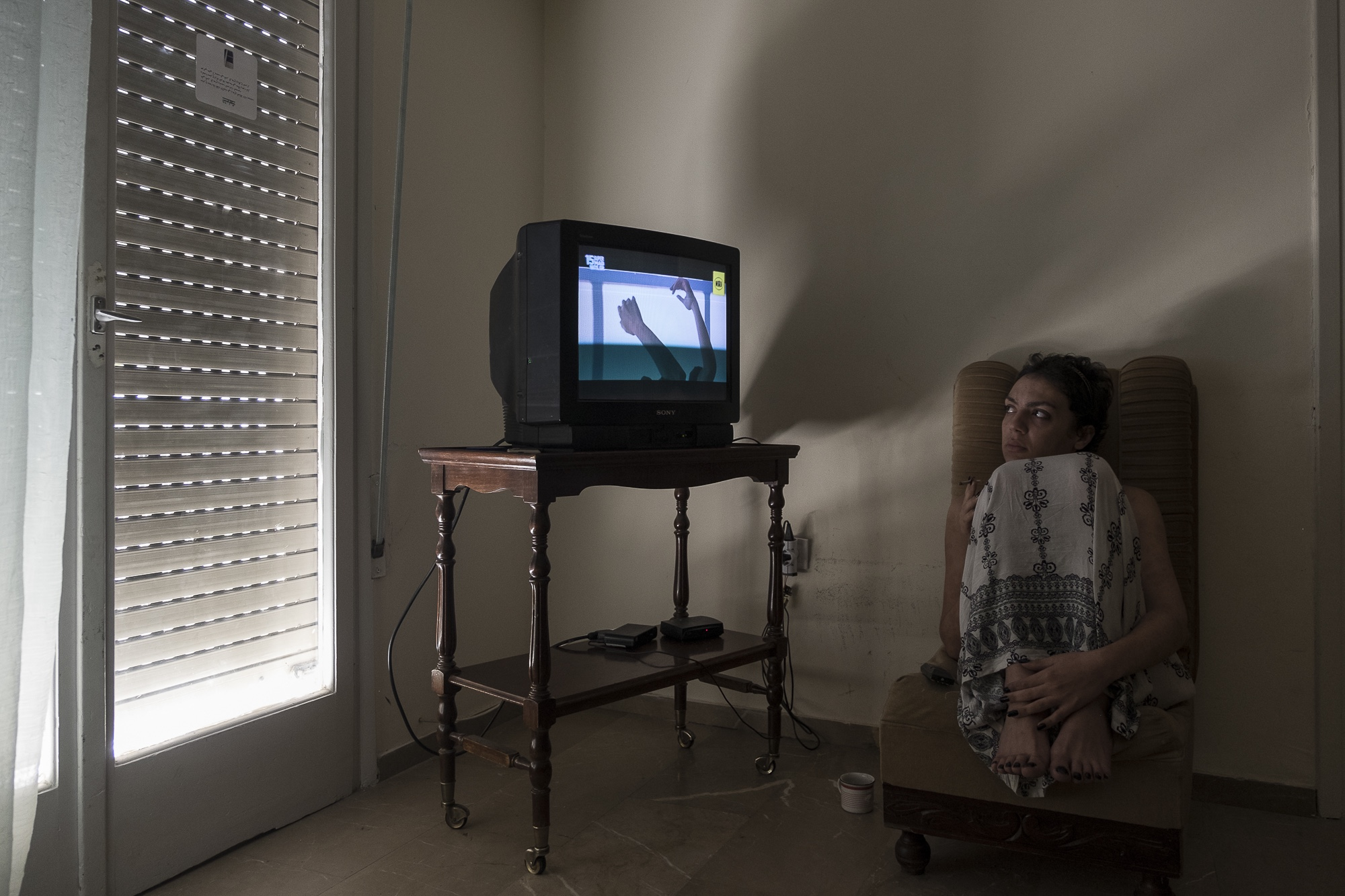 Y., 28, a transgender woman from Morocco watches TV while relaxing at her apartment in Athens, Greece. July 13, 2017