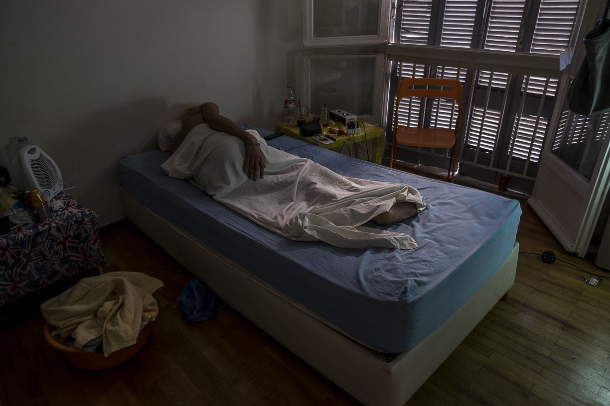M., a transgender woman from Tunisia, takes a nap at her apartment in Athens, Greece. September 4, 2017