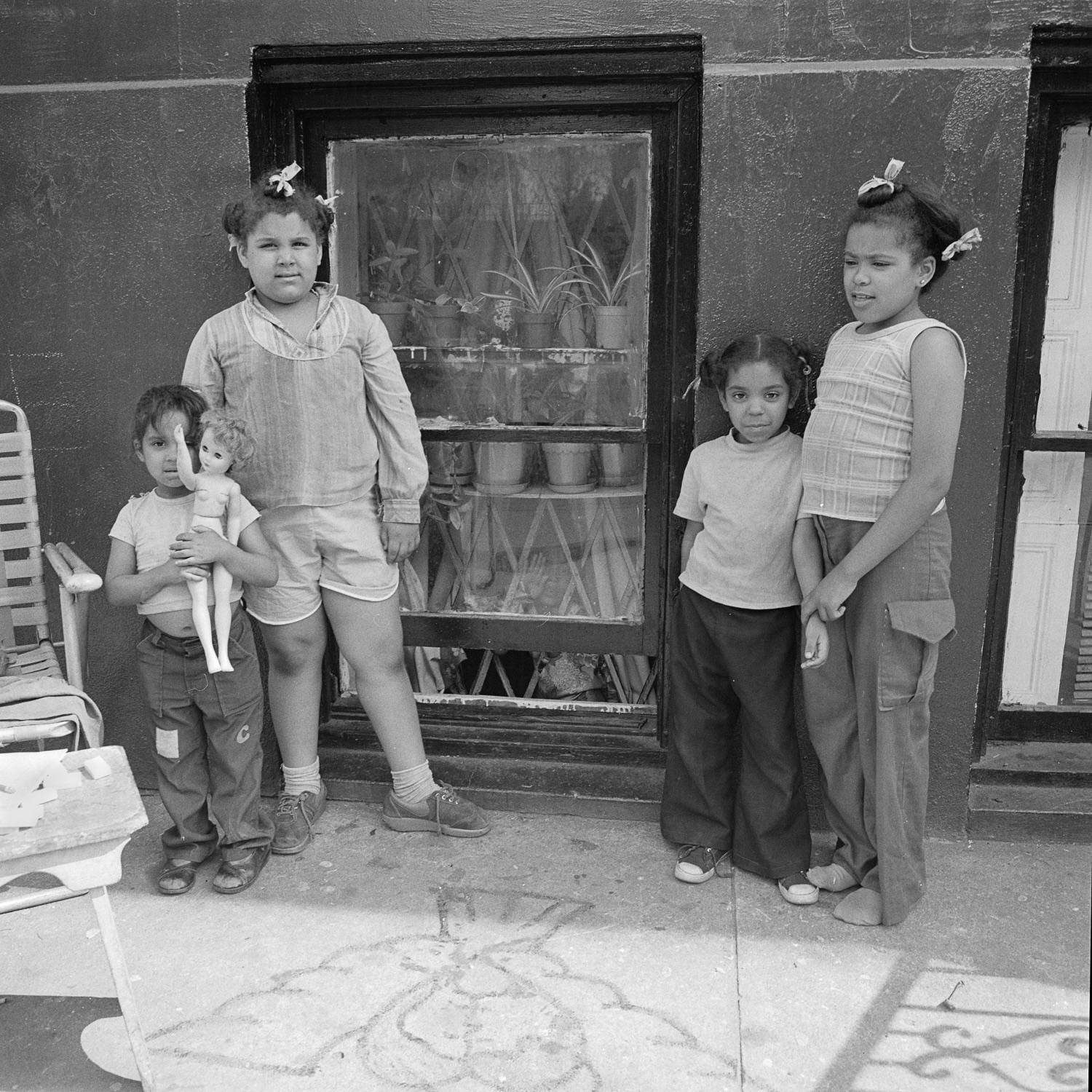 Four kids and a doll in front of a window NY, NY June 1978