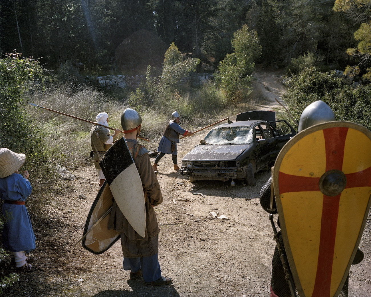 February 24, 2017. Peru Forest near Latrun, Israel. As a little joke, an Israeli reenactment group departs from the historical protocol and slams away at a car wreck. The historical era they are devoted to is that of the crusades. At the Council of Clermont on November 27, 1095, Pope Urban II invoked the Christians to crusade in the Holy Land. They should drive away the Muslims living there and seize the holy sites in Jerusalem for the Christians.