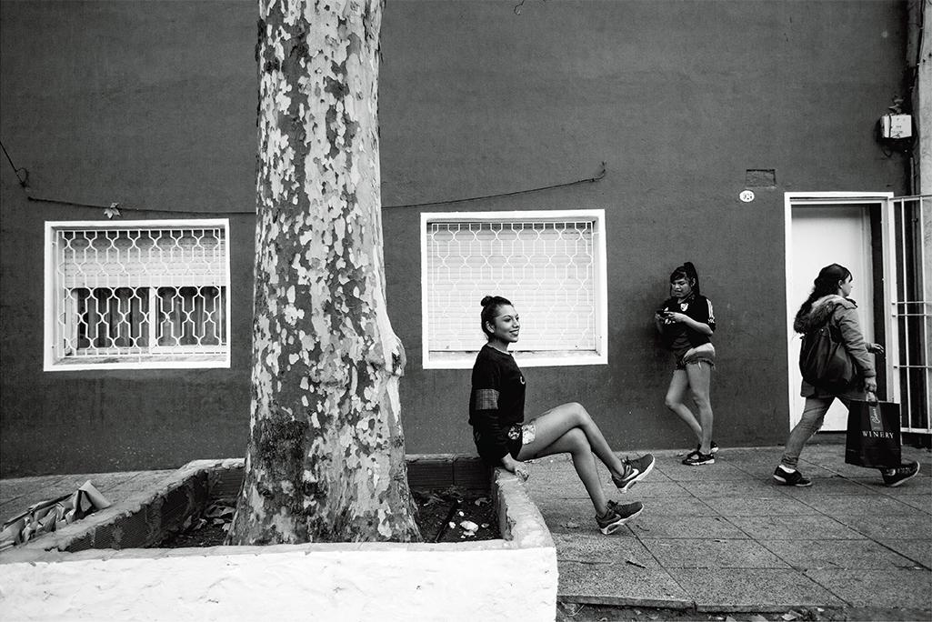 A smiling Rihanna Rios sits in front of El Gondolín.