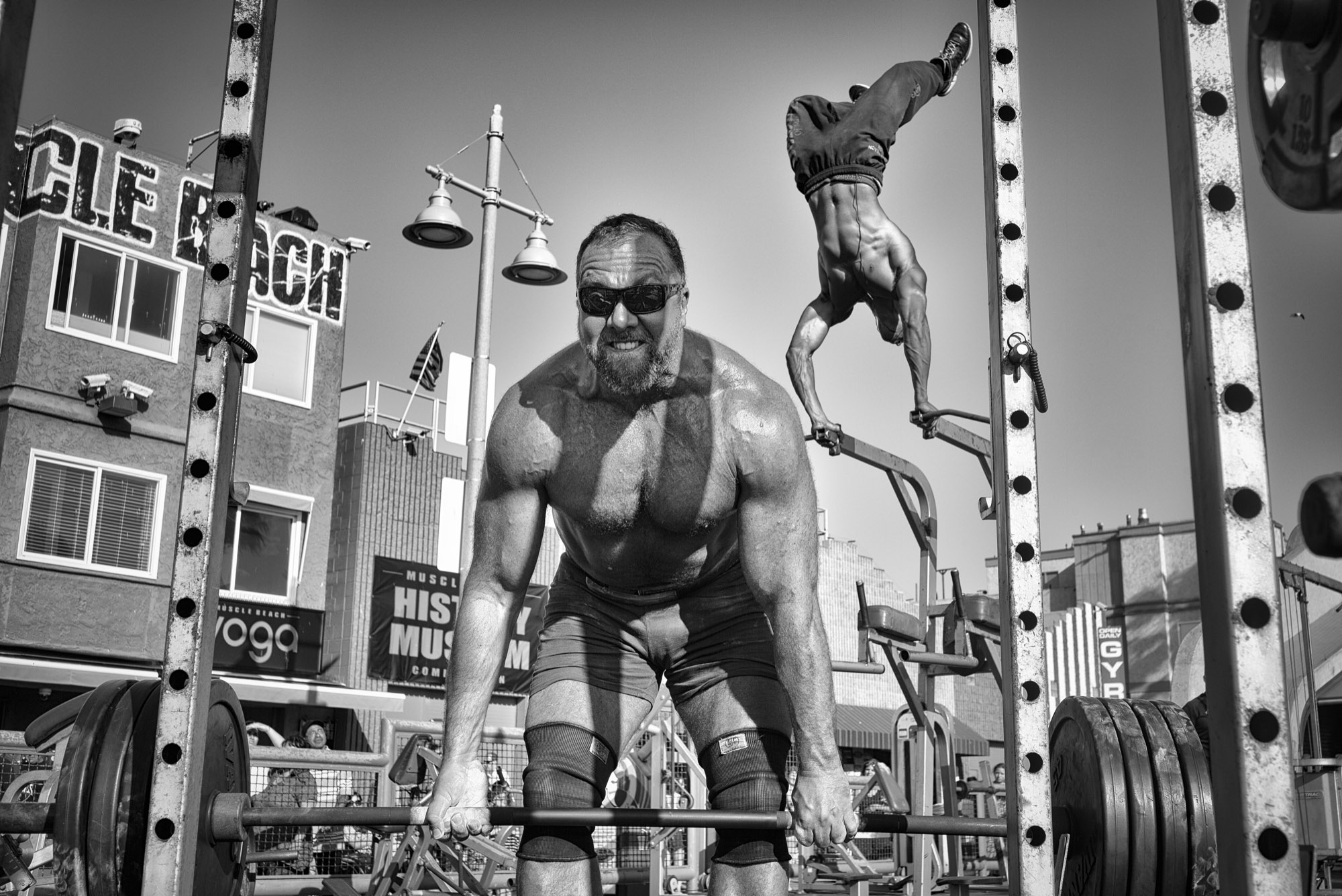 A weightlifter raises a barbell loaded with heavy plates while Ike Catcher performs an aerial handstand at the world-famous Muscle Beach Gym. © Dotan Saguy