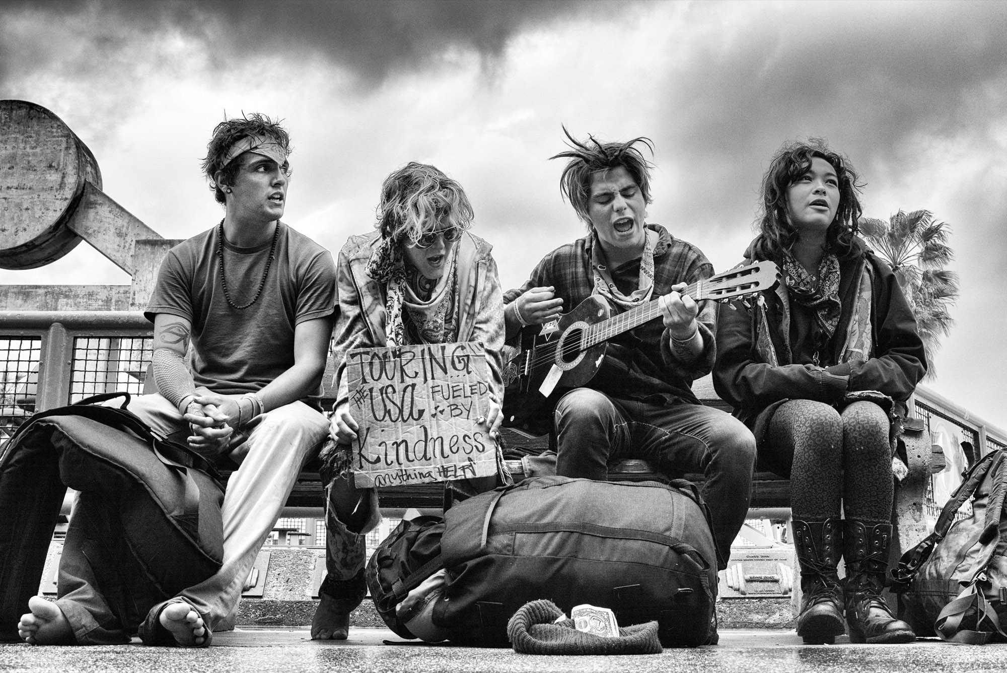 A group of young hippies sing on a bench across from the Muscle Beach Gym. © Dotan Saguy