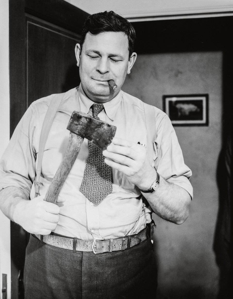 A cigar-chomping detective examines the murder weapon, ca. 1940. Copyright: Cliff Wesselmann Photo Courtesy of Gregory Paul Williams, BL Press LLC / TASCHEN