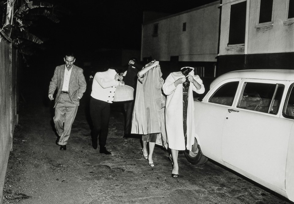 A bevy of hookers cover up after a vice squad raid at the Carolina Pines Restaurant on Melrose Avenue, ca. 1957. Copyright: Cliff Wesselmann, Photo Courtesy of Gregory Paul Williams, BL Press LLC / TASCHEN