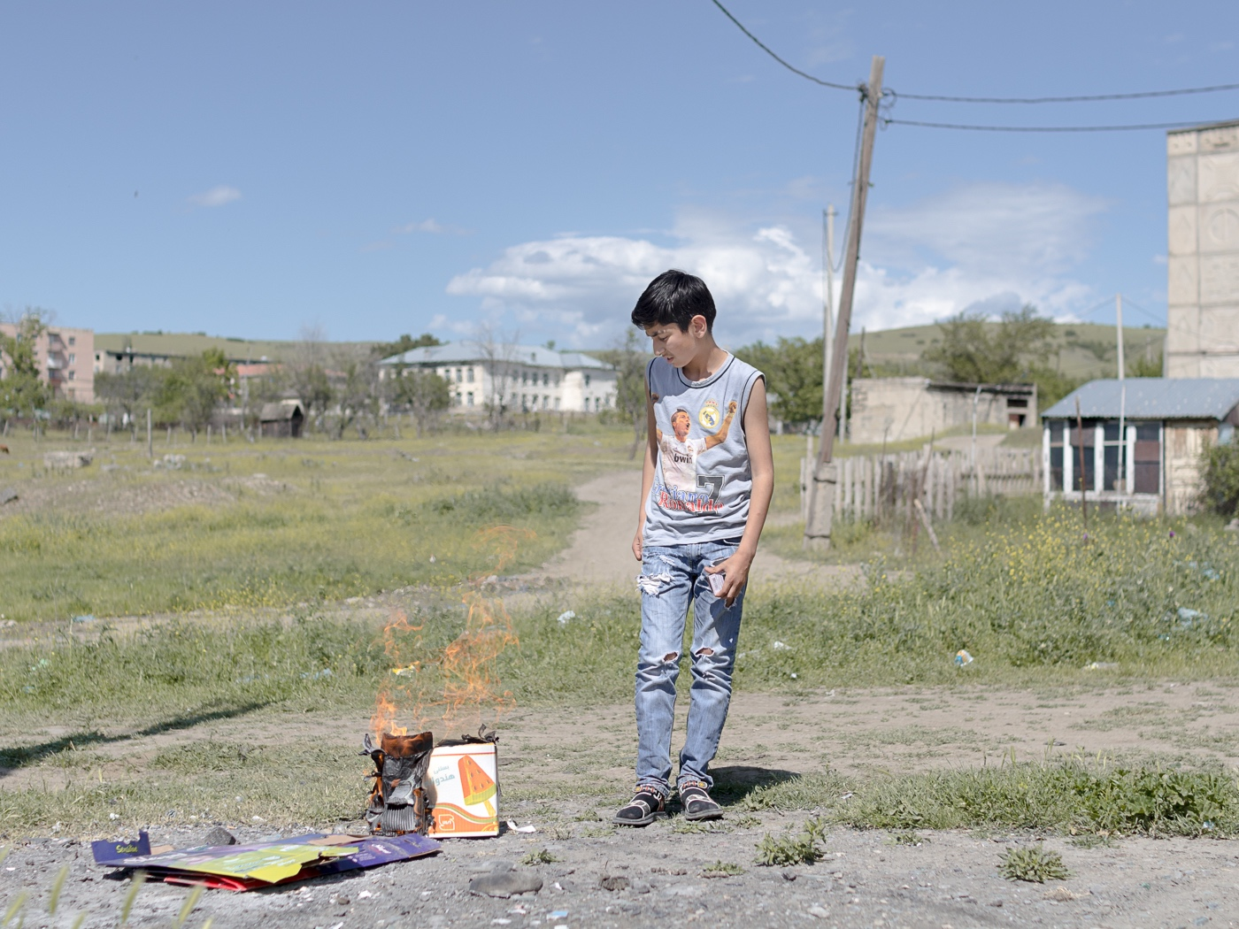 A boy burns collected garbage in the center of the settlement. Children struggle to find activities in Vaziani. The parents in the settlement worry about the future of their kids, thus they try to give them better prospects in life through education.