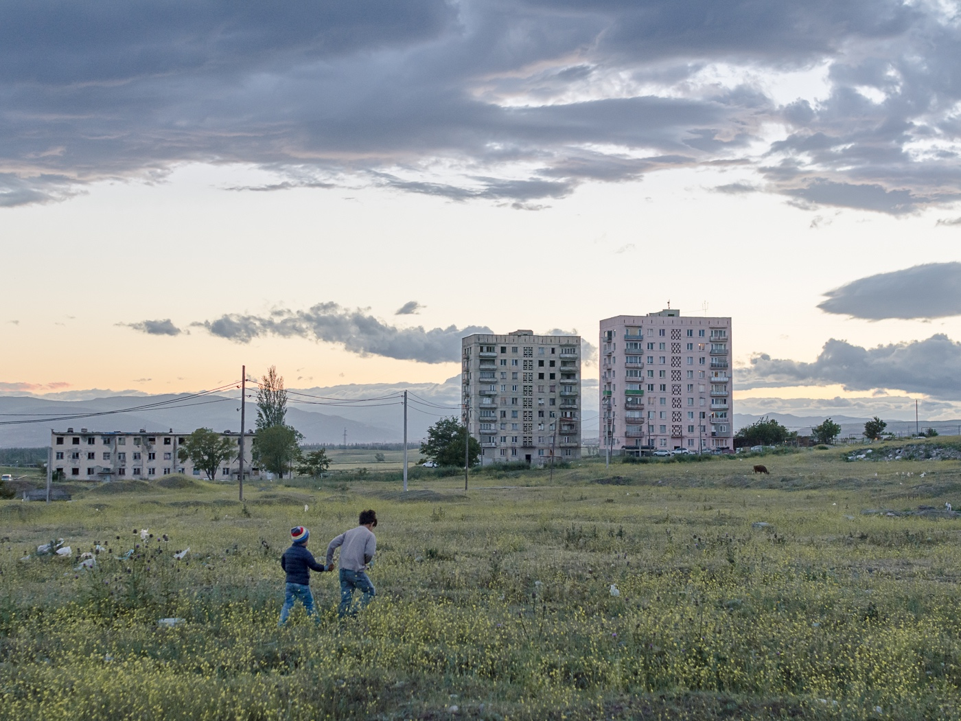Two children roam around the broad fields at the periphery of the settlement. In demand for a suited playground, the inhabitants collected signatures for a petition to the government – they only received empty promises in return.