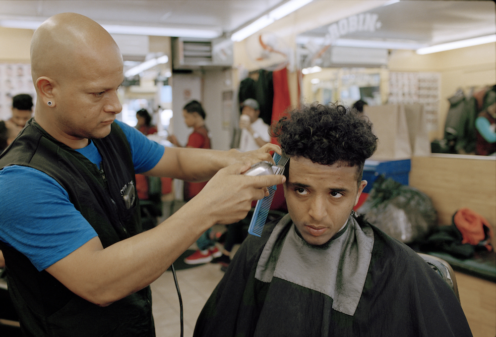 Ahmed Alzandhani gets a medium skin fade the day before a soccer match at a Dominican barbershop in the Flatbush neighbourhood of Brooklyn.