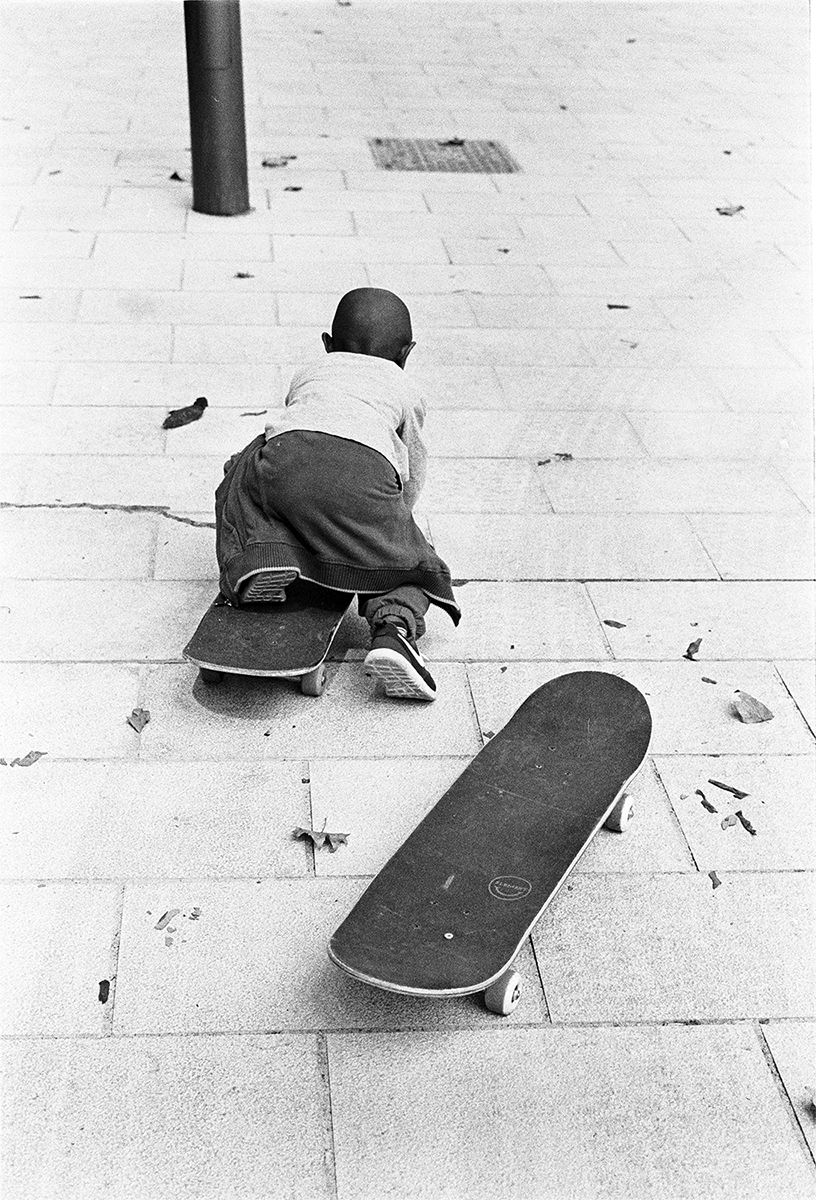 A young boy lies on a skateboard and pushes themself along
