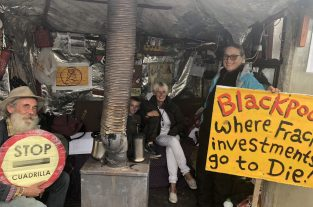A collection of protesters inside a manmade shelter holding signs protesting fracking