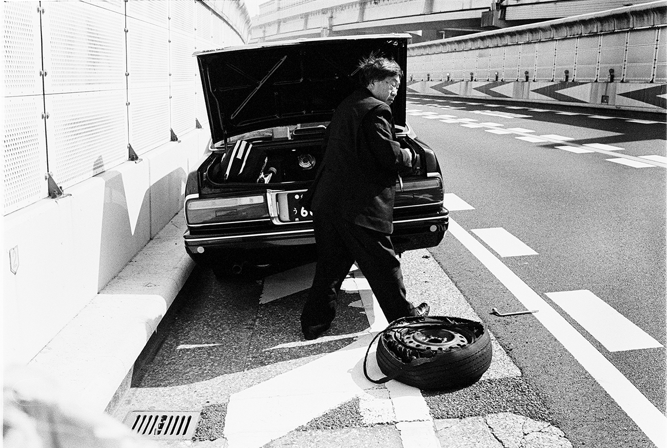 A man in a suit changes the tire of a taxi parked on the side of the road
