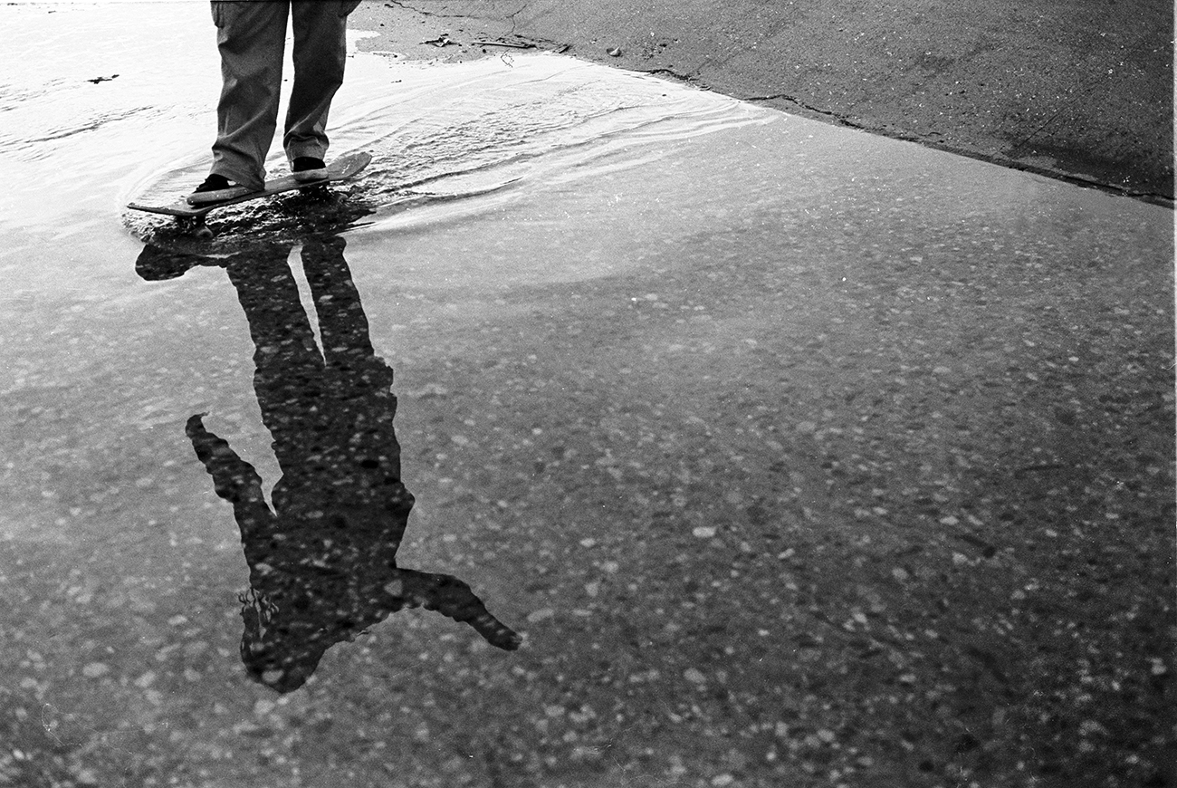 The reflection of a skateboarder in a puddle as they skate through