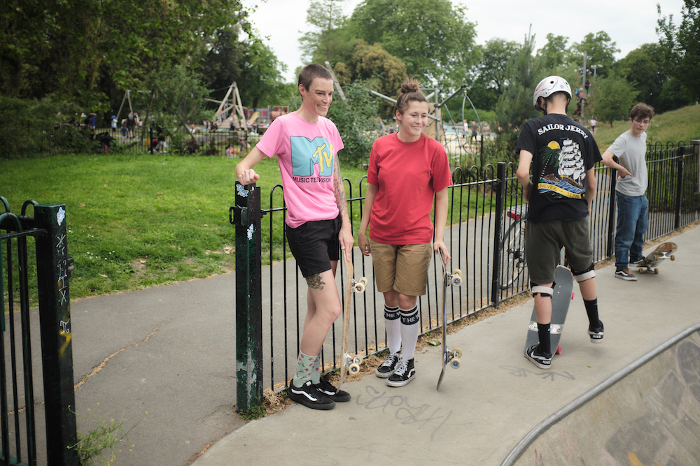 A number of skaters stand around the edge of a skatebowl