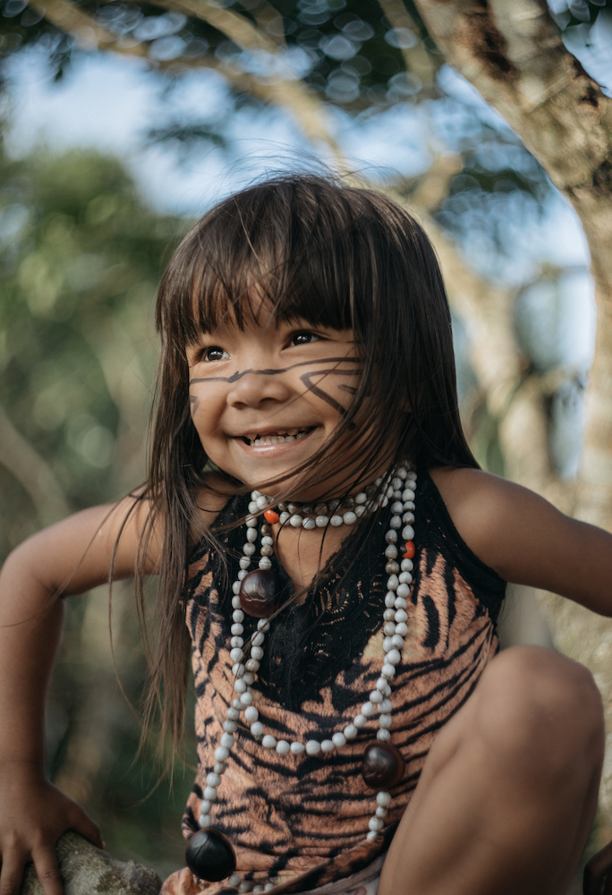 A young indigenous brazilian child wearing traditional clothing with facepaint