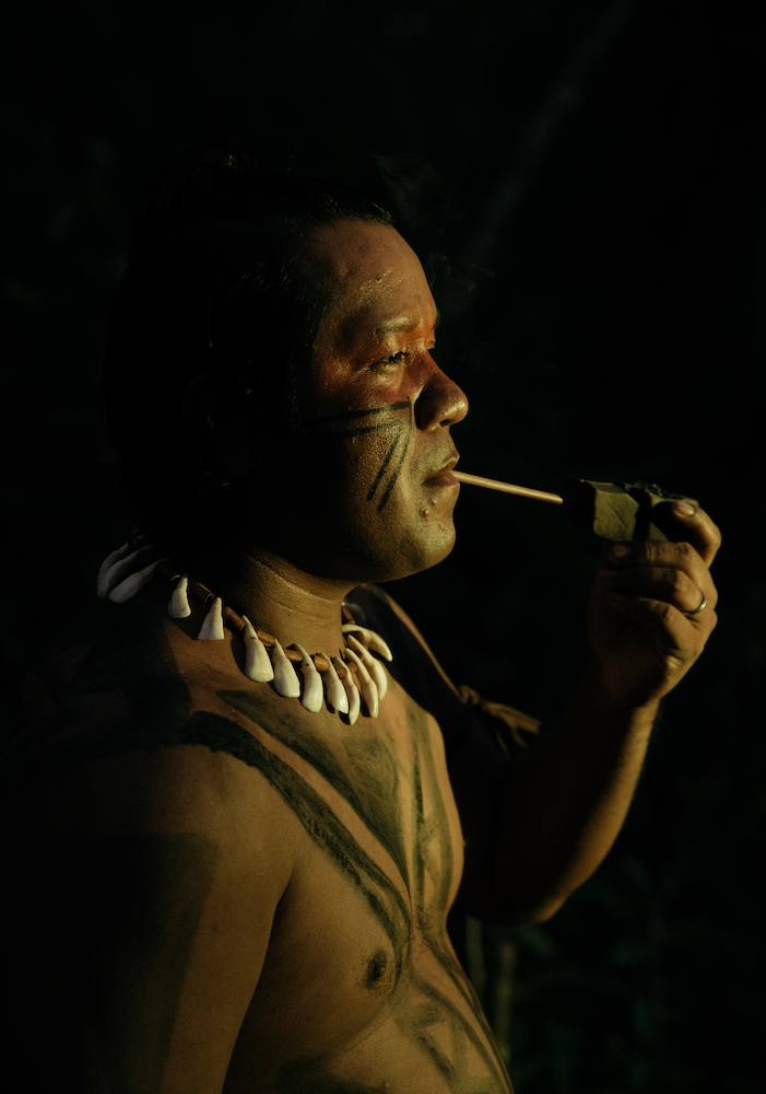 an indigenous brazilian man smokes a carved pipe. He is shirtless with his chest adorned in body paint and wears a necklace.