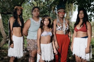 A group of indigenous brazilian women in a forest clearing wearing traditional clothing