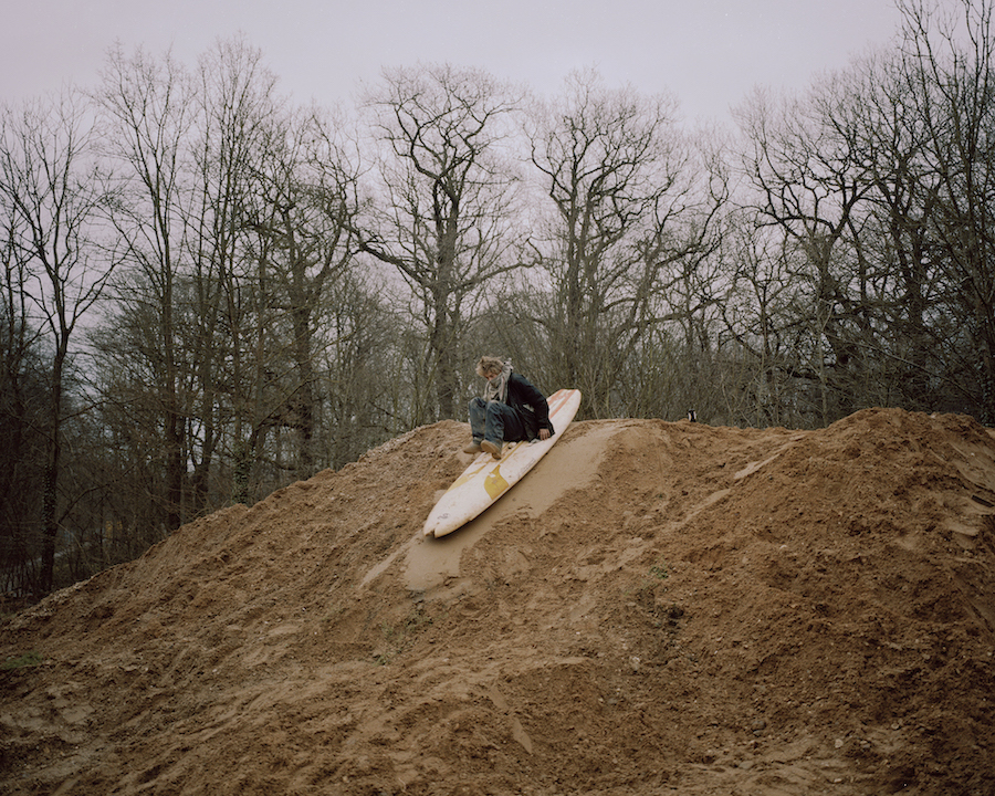 A figure slides down a pile of mud on a surfboard