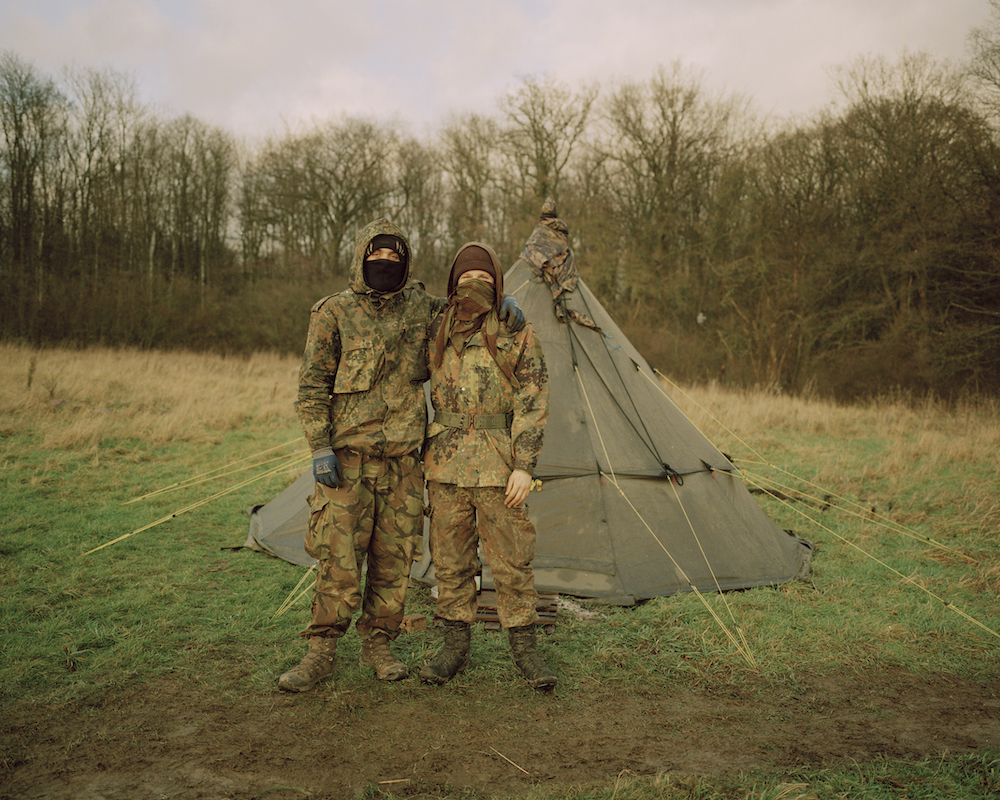 Two ecoactivists in camouflage pose in front of their tent