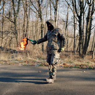An ecoactivist holds a burning molotov cocktail