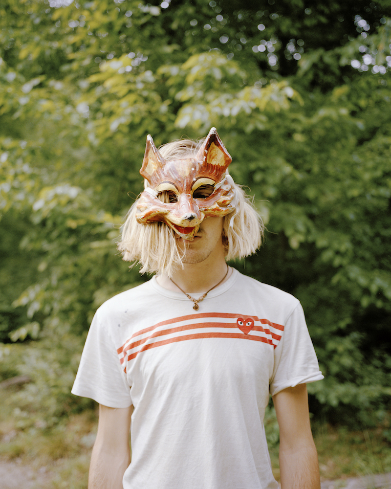 A young man poses for a portrait with a fox mask covering the top of her face