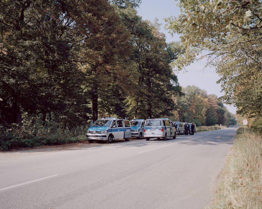 A row of police vehicles line up along the side of the road at Hambach Forest