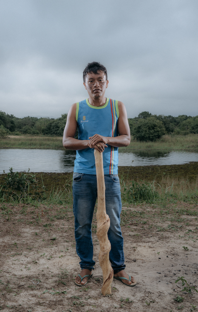 An indigenous Brazilian man standing in front of a small lake. He wears modern clothing and rests his hands on top of a large, carved wooden club.