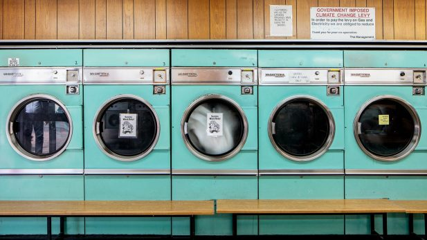 A row of bright turquoise laundry machines